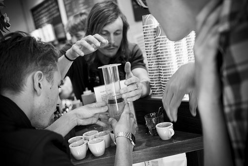 Baristas using an AeroPress, pouring into small white coffee cups - Tin Cup Coffee Company Nashville, TN
